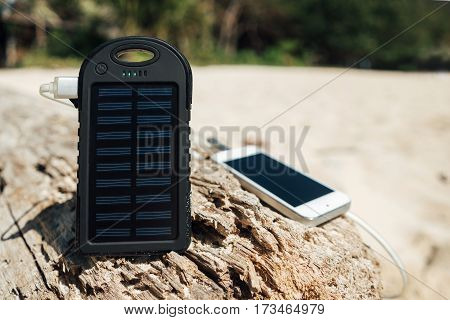 Battery solar energy device on a background of the sandy beach of an uninhabited island. Charge smart phone from the solar battery.