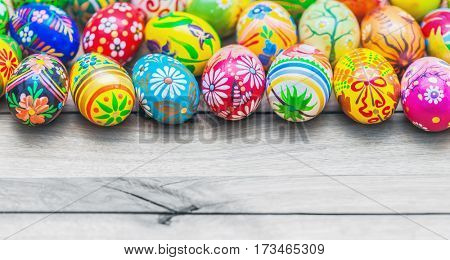 Easter handmade eggs painted in colorful floral patterns placed on wooden table.