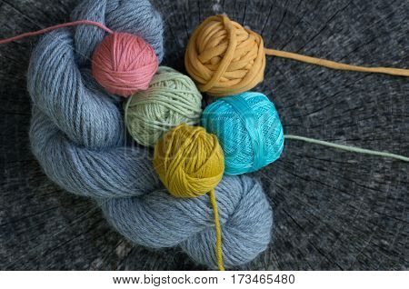 Knitting Yarns Of Various Colors On Tree Stump Background