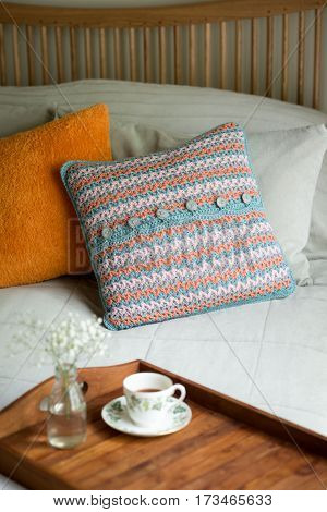 Pillows And Wooden Tray With Tea And Blooms In Bed