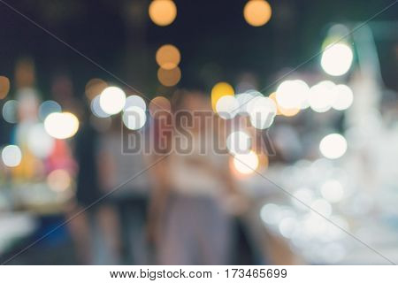 People Walking At Festival Event Party Night And Bokeh Blurred Background.