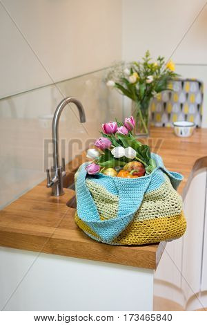 Fruits And Flowers In Crocheted Bag On Kitchen Counter