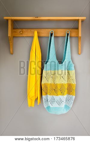 Crocheted Bag And A Yellow Towel Hanging On Wall Rack