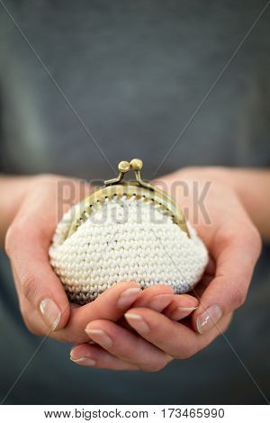 Hands holding a white knitted woolen coin purse