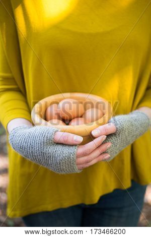 Hands In Woolen Gloves Holding Bowl Of Eggs