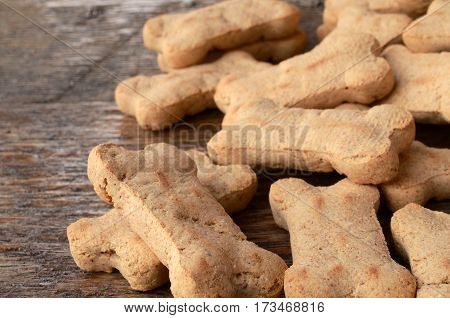 A close up image of bone shaped dog treats spilled on a wooden table.