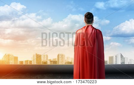 A businessman in superman cape standing turned back on the sky background with cityscape below. Business hero. Confidence and success. New opportunities.