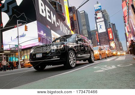 New York February 21 2017: A Range Rover SUV and a string of yellow cabs behind it are seen in traffic on Broadway at Times Square.
