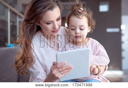 Woman and her child girl relaxing at tablet computer.