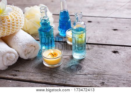 Spa or wellness setting in blue yellow and white colors. Bottles wih essential aroma oil towels candles and wisps on wooden background. Selective focus. Place for text.