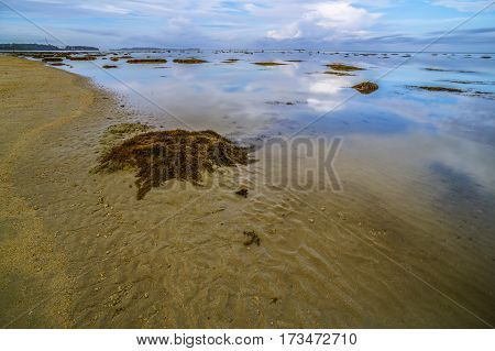 Calm sea,reflection and cloudy sky during low tide. Reflection of the vibrant sky and moving cloudy.