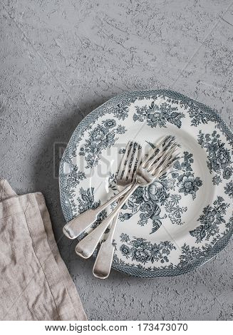 Vintage style plate and forks on a grey table top view