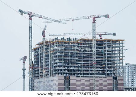 modern urban hiht building under construction with a crane. Construction of the new building. Construction cranes