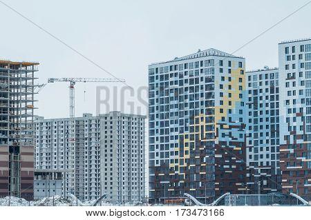 modern urban high building under construction with a crane. Construction of the new building. Construction cranes. new modern residential quarter, area