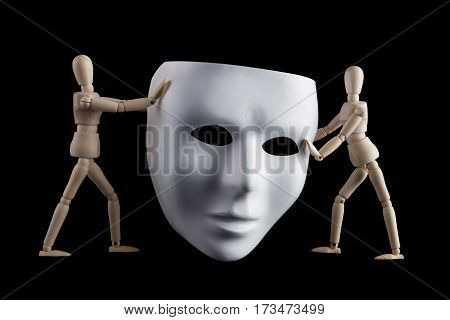 Two wooden figurines holding a white human face mask isolated on black background. Anonymity and facelessness concept