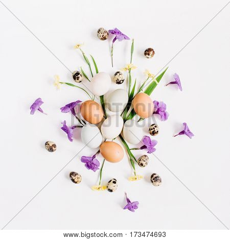 Easter eggs quail eggs yellow and purple flowers on white background. Flat lay top view. Traditional spring concept. Easter concept.