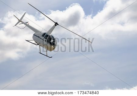 Light private helicopter flying in cloudy sky