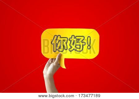 Human Hands Holding 'Nihao' Yellow Speech Bubble Over Red Background - Chinese language learning concept