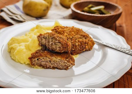 Fried minced meat with cheese and mashed potatoes on white plate