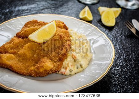 Pork fried schnitzel with traditional potato salad on black stone table