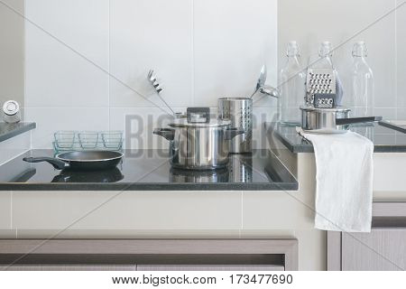Stainless steel kitchenware on black top counter