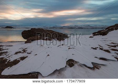 Beautiful snow formation and boulder nearby frozen lake on sunrise