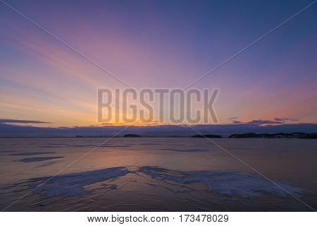 Textured snow formation on ice surface of frozen lake on sunrise