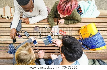 Top view of multiracial friends using mobile smart phone - Addiction concept with young people on new tech devices - Multicultural students having fun on social media networking - Warm vivid filter