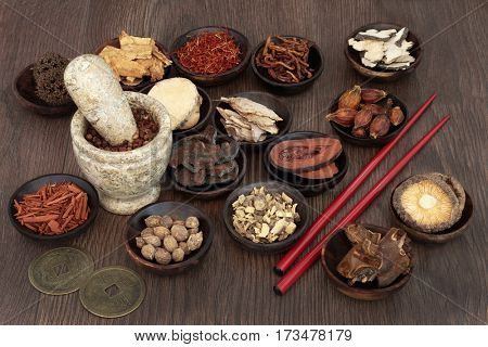 Chinese apothecary herb selection used in traditional herbal medicine with mortar and pestle, chopsticks and feng shui coins for good health and success.