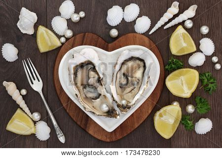 Oysters and pearls on a heart shaped plate on a maple wood board with lemon fruit, parsley, shells and an old silver fork over old oak background.