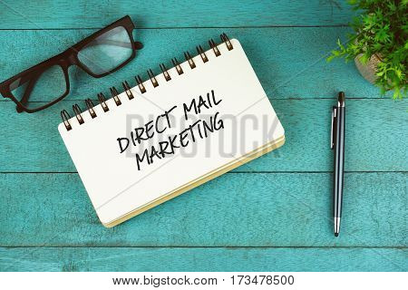 Business Concept. Top view of eye glasses, plant, pen and open notebook written with Direct Mail Marketing on blue wooden background.