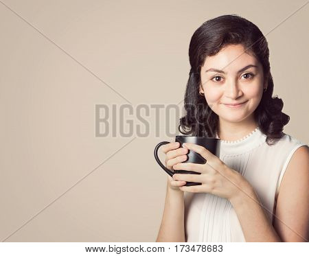 happy smiling woman in casual clothes holding white cup of coffee or hot beverage on plain background room for copyspace