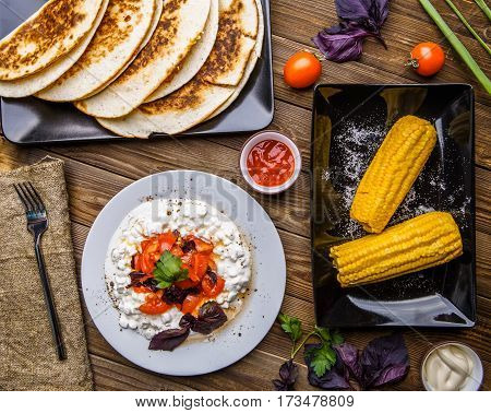 Quesadilla, salad with cottage cheese and tomatoes, two corn on wood table. Top wiev. Fresh dinner.