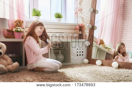 Cute little child is combing near mirror. Happy girl is having fun in kids room at home.