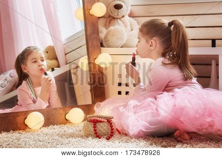 Happy girl dresses up at home. Funny lovely child is having fun with lipstick in kids room.
