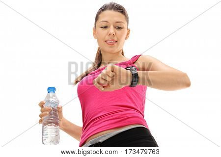 Female athlete holding a bottle of water and looking at her smartwatch isolated on white background
