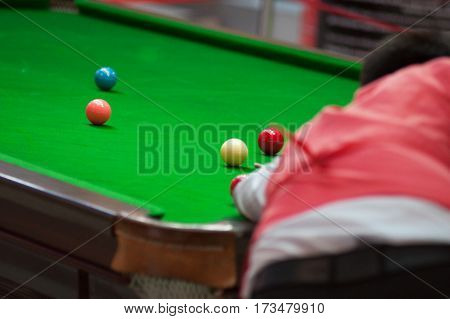 A man plays snooker does hit the fuzzy balls from the back