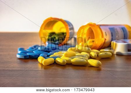 Two prescription bottles overturned with yellow and blue pills spilling out on the table. Pills are in focus with the bottles out of focus.