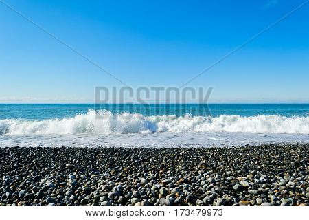 Sea waves breaking on a stony beach, forming sprays and splashes