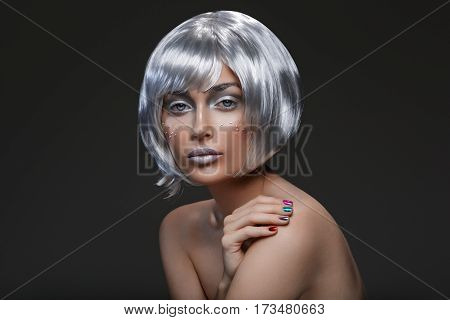 Beautiful young woman with glowing skin, fashion make-up and metallic nails in short silver hair wig. Beauty shot on black background. Copy space.