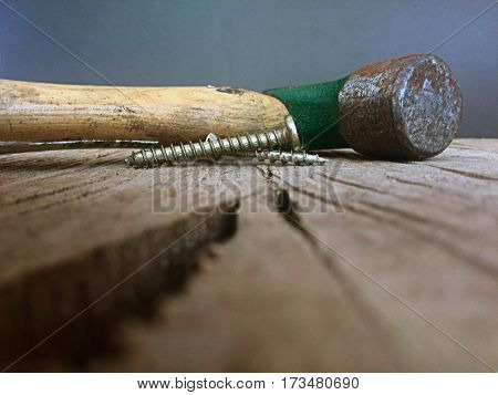 close up of hammer and screws on blurred cracked wood