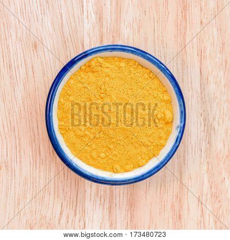 Curcuma powder in bowl on wood floor background.