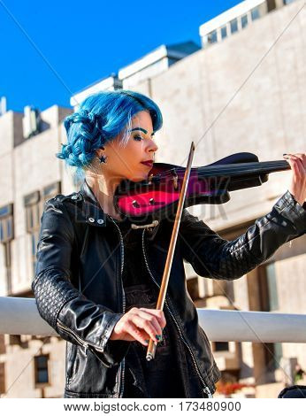 Woman perform music on violin in park outdoor. Girl performing jazz on city street . Spring outside with blue hairstyle background.
