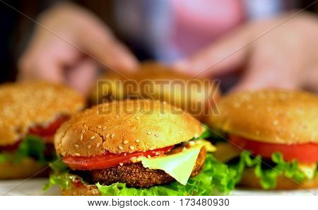 Mini hamburger buns. Fast food with ham on wooden board . Group of hamburger. Human hand holding cheeseburger. Sharpness in front of sandwich.