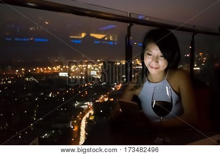 asian lady read message on mobiel at luxury restaurant in the night, bangkok, asia