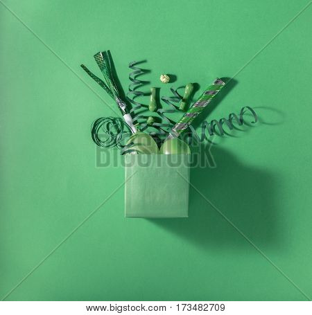 Green gift box with various party confetti balloons streamers and decoration on a green background. Flat lay