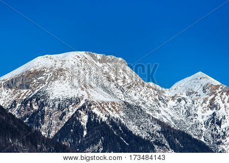 Snowcapped Julian Alps and clear sky behind as copy space
