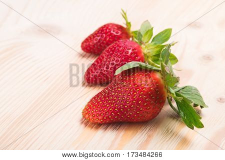 Three strawberries on a white board as background