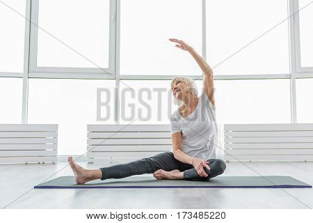 Happy senior lady is going for sports. She is sitting and stretching arm up. Lady is smiling