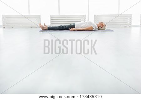 Serine old woman is lying on mat before exercising. Focus on floor